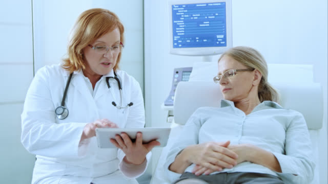 Doctor advising patient with the help of tablet