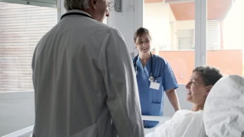 vídeos y material grabado en eventos de stock de un médico y una enfermera visitan a un paciente recuperándose en la cama de un hospital. - ubicaciones geográficas