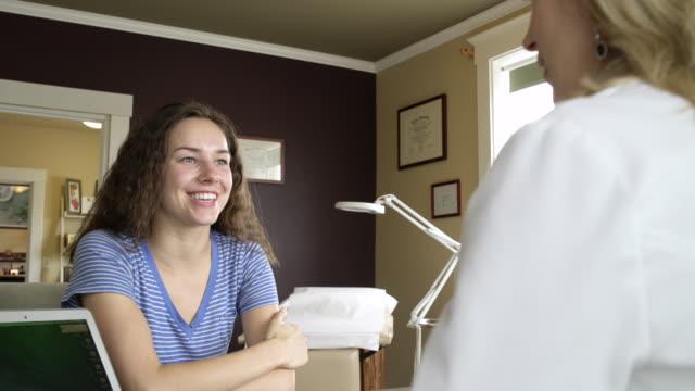 vídeos de stock, filmes e b-roll de a doctor and a patient having a discussion - dermatologia