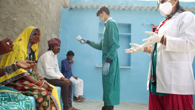 doctor and essential services staff going door to door survey to inform and educate family about the pandemic and to take precautions, safe distance and measure temperature - village stock videos & royalty-free footage