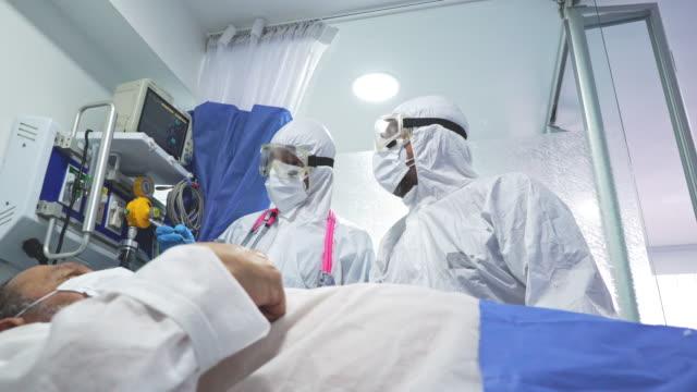 医師と女性医師は、熱心な19パンデミックの間に安全プロトコルで高齢患者を治療しています - レスピレーターマスク点の映像素材/bロール