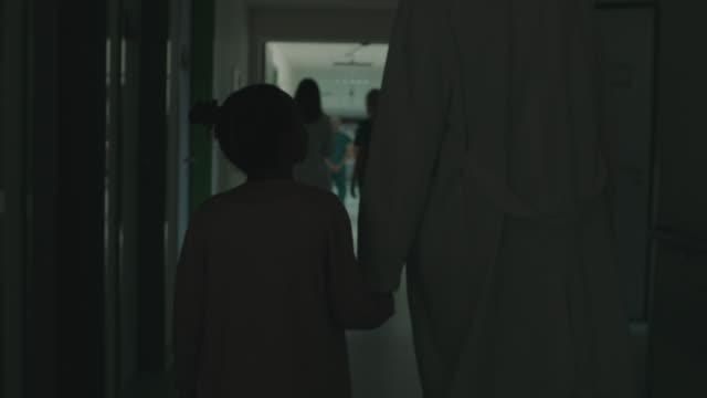 vidéos et rushes de mains de fixation de docteur et de fille et marchant à l'hôpital - personne non reconnaissable