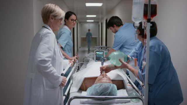 DS Arzt und medizinischem Team übertragen Patienten auf Trage