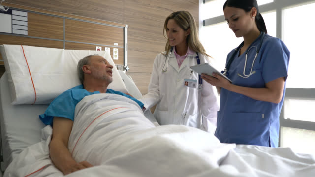 doctor and hospitalized senior patient talking while nurse looks at medical chart on tablet all smiling - hospital bed stock videos & royalty-free footage