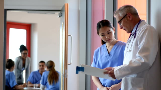 doctor and nurse checking medical charts. - nhs stock videos and b-roll footage
