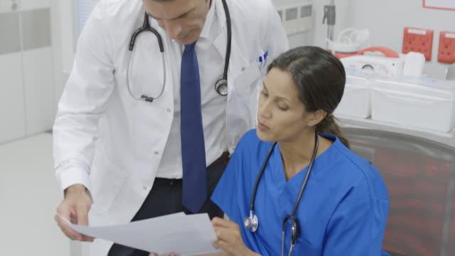 Arzt und Krankenschwester diskutieren über Dokumente