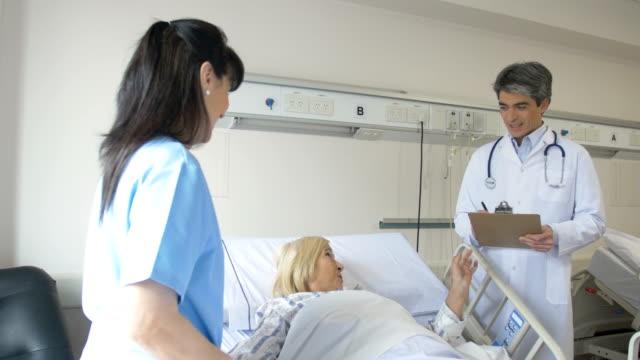 vidéos et rushes de médecin et infirmière examinant le patient senior - infirmière