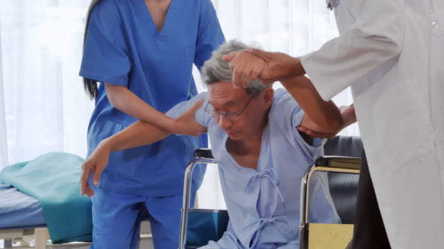 Doctor and nurse helping a patient to lie down to elderly man at his bedside.A sick elderly staying at a hospital.Caring medical worker in hospital.Medical, age, health care, cardiology and people concept.Healthcare: Caretaking