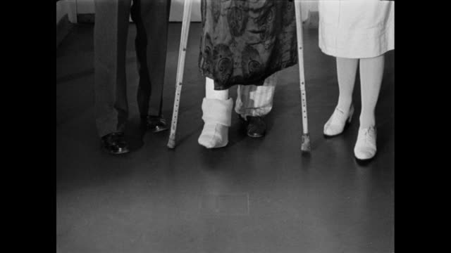 TU A doctor and nurse helping an injured patient walking with crutches / United Kingdom