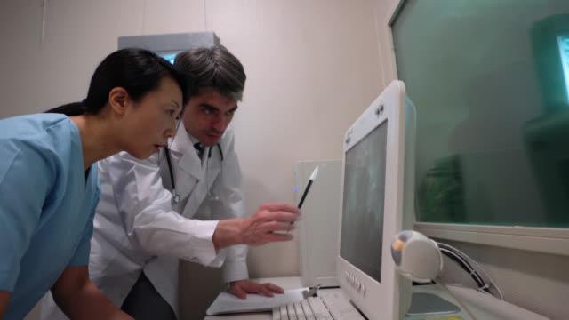 arzt und krankenschwester betrachten ein xray und notizen in zwischenablage - knochen im beckenbereich stock-videos und b-roll-filmmaterial