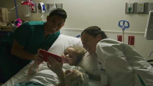 vídeos de stock, filmes e b-roll de doctor and nurse posing for cell phone selfie with girl in hospital bed / salt lake city, utah, united states - confiança
