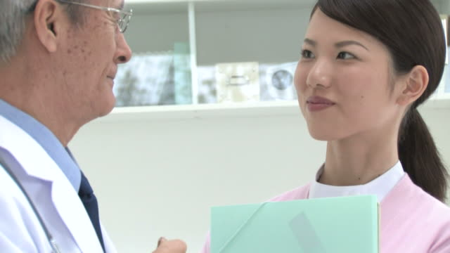 doctor and nurse smiling at each other - angesicht zu angesicht stock-videos und b-roll-filmmaterial