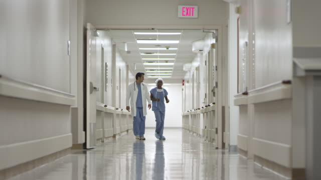 WS Doctor and Nurse talking and walking in hall / Houston, Texas, United States
