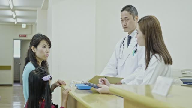 läkare och sjuksköterska pratar med mor och hennes dotter i lobby - sjuksköterskereception bildbanksvideor och videomaterial från bakom kulisserna