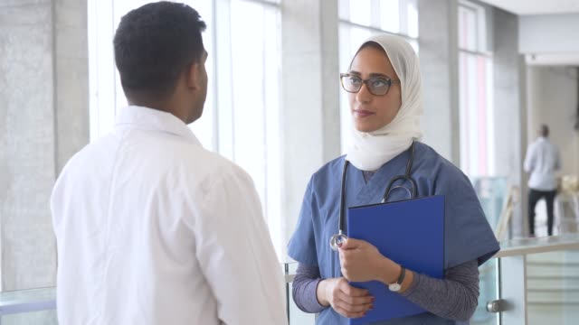 doctor and nurse talking - hijab stock videos & royalty-free footage