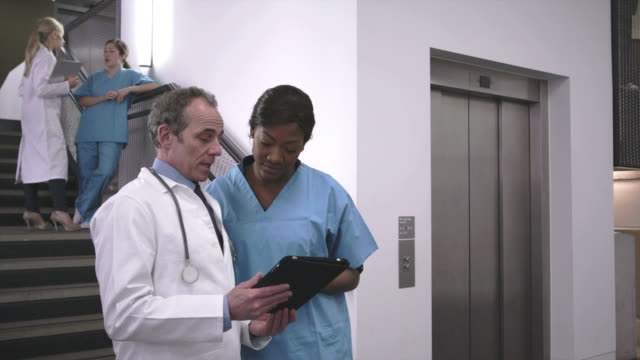 doctor and nurse using tablet - legs crossed at ankle stock videos and b-roll footage