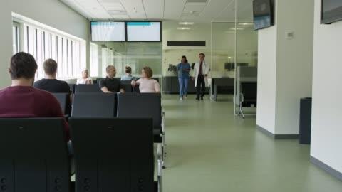 vídeos y material grabado en eventos de stock de doctor y enfermera caminando por pacientes en corredor - pasillo característica de edificio