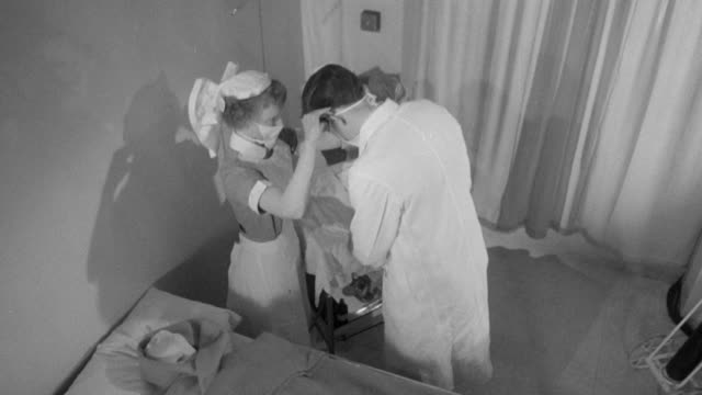 1958 ha doctor and nurses starting a blood transfusion for a patient / united kingdom - anno 1958 video stock e b–roll