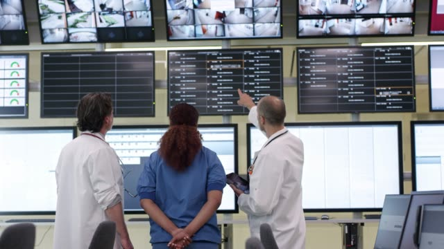 Doctor and nurses talking while looking at screens