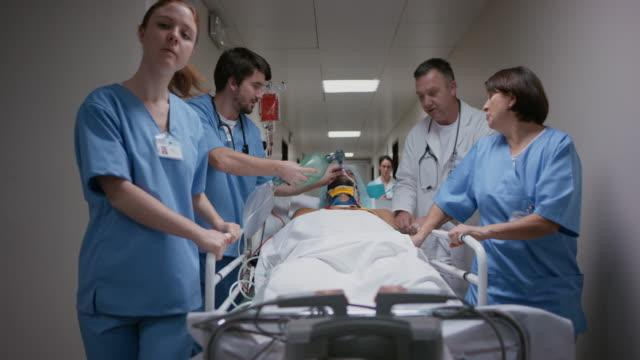 ds arzt und krankenschwestern transport patienten krankenhaus korridor hinunter - erste hilfe stock-videos und b-roll-filmmaterial