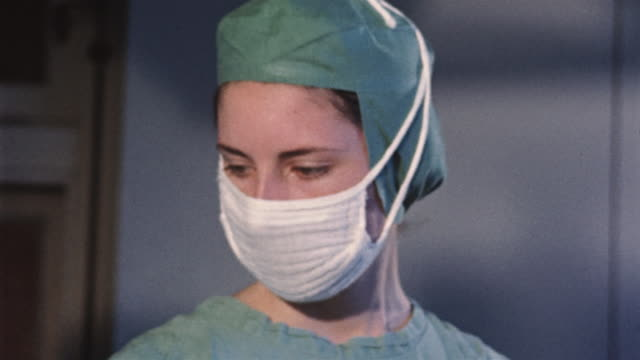 stockvideo's en b-roll-footage met 1955 montage doctor and nurses wearing surgical masks and scrubs during surgery/ usa - operatiekamer