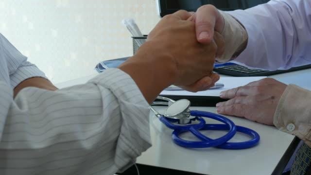 vídeos de stock, filmes e b-roll de médico e paciente, aperto de mão - médico geral