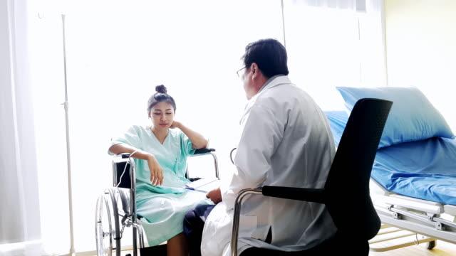 vídeos de stock, filmes e b-roll de médico e o paciente sente-se na cadeira de rodas no quarto do hospital - perguntando