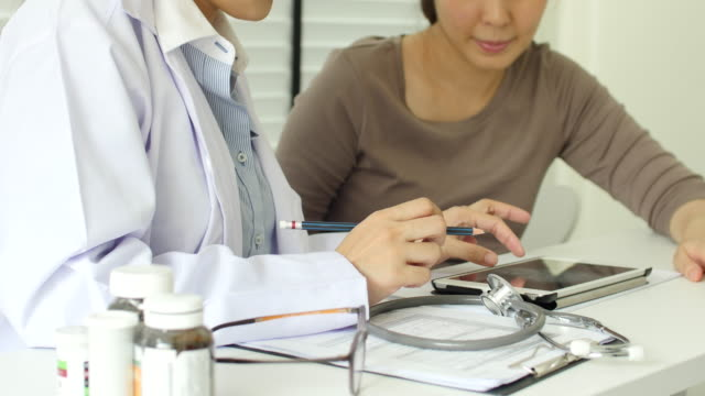 Doctor and patient talking with Digital tablet in office