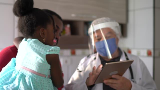 vídeos de stock, filmes e b-roll de médico e pacientes (pai e filha) em consulta médica na casa do paciente - examinar