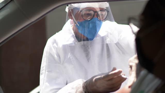 vídeos de stock, filmes e b-roll de médico aplicando vacina em um paciente em uma unidade através - usando desgaste do trabalho de proteção - meio de transporte