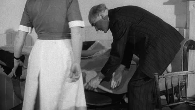 1952 montage doctor arriving to tend to injured patient, greeting district nurse and kneeling down beside couch to examine injured leg and foot, nurse bringing doctor bandages / wadhurst, england, united kingdom - visita a domicilio video stock e b–roll