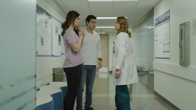 doctor arriving with bad news and talking with waiting couple in hospital corridor / salt lake city, utah, united states - ehefrau stock-videos und b-roll-filmmaterial