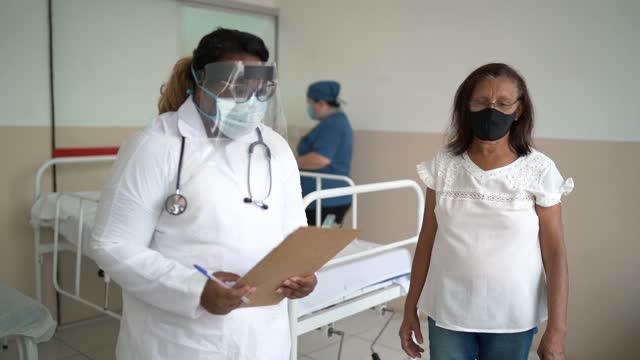 vídeos de stock, filmes e b-roll de médico fazendo perguntas ao paciente e preenchimento de formulário no hospital - usando máscara facial - controle