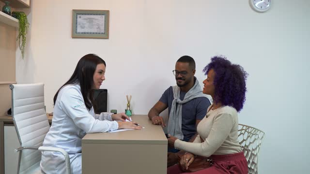 vídeos de stock e filmes b-roll de doctor attending a young couple - confiabilidade