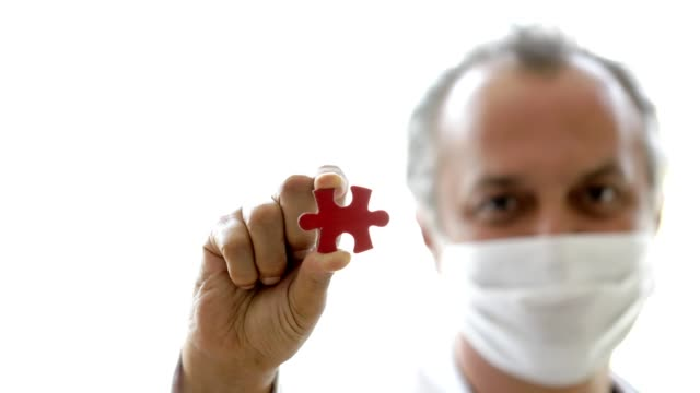 medico dietro la maschera di protezione che mostra il pezzo mancante del puzzle - puzzle video stock e b–roll