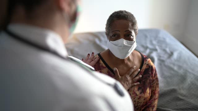 doctor care of senior woman patient on medical visit at her house - using face mask - examining stock videos & royalty-free footage