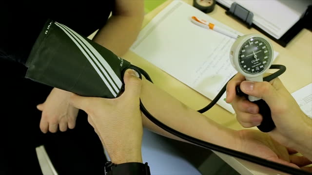 Doctor checking blood pressure of a patient at hospital.close up