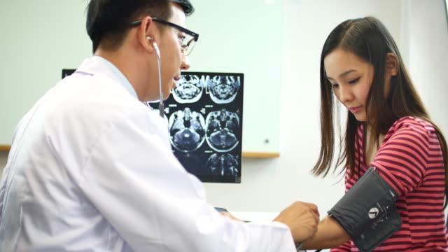 若い女性のチェック血圧を医師します。 - 医療診断点の映像素材/bロール
