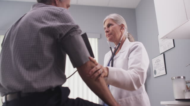 doctor checking blood pressure of middle-aged male patient - visit stock videos & royalty-free footage