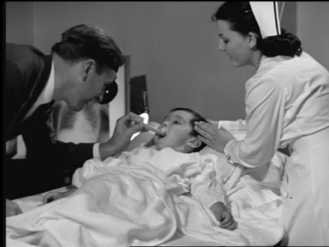 b/w 1948 ms doctor checking boy's throat + ears with nurse assisting in hospital room - boy medical exam stock videos and b-roll footage