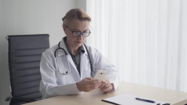 läkare kontrollera data av patient på mobiltelefon vid skrivbord sjukhus rum - luta sig tillbaka bildbanksvideor och videomaterial från bakom kulisserna