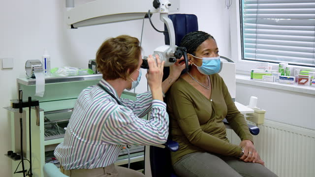 ent doctor checking ear of woman patient at clinic - human ear stock videos & royalty-free footage