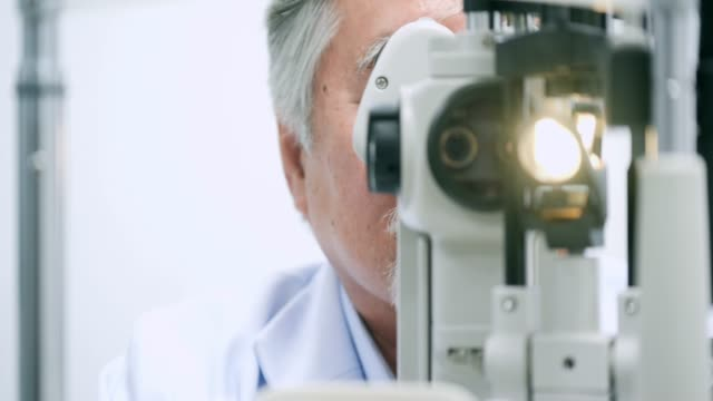 Doctor checking eyes of a senior male patient.Optician examining a patients eyes in ultra