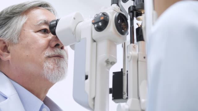doctor checking eyes with biomicroscope device 4k. dolly shot of  doctor examining eye structure with help of medical equipment. professional health care. - esaminare video stock e b–roll