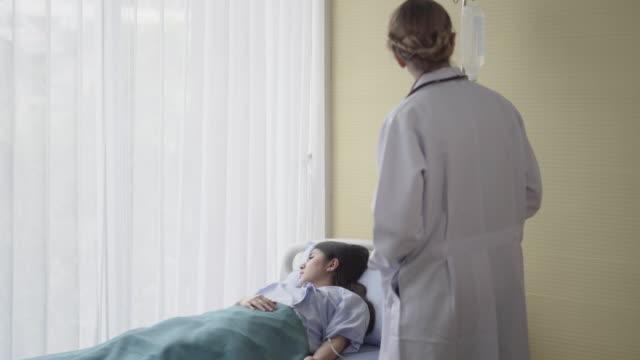 läkare kontrollera kvinnlig patient på sängen i sjukhussal - luta sig tillbaka bildbanksvideor och videomaterial från bakom kulisserna