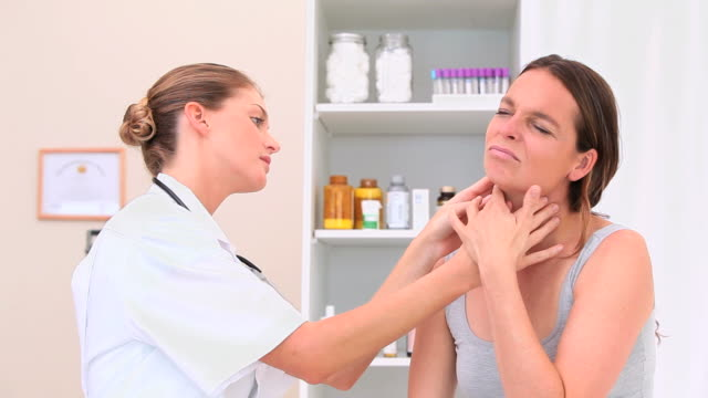 Doctor checking glands of a patient