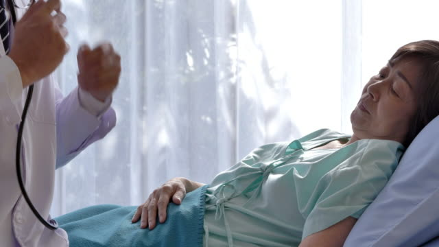 vídeos de stock, filmes e b-roll de médico verificando o coração dela. masculino médico examinador sênior paciente do sexo feminino no quarto do hospital. - estetoscópio
