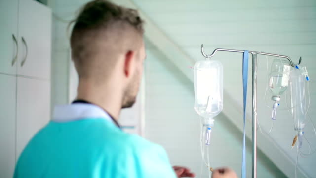 doctor checking infusion system - saline stock videos and b-roll footage