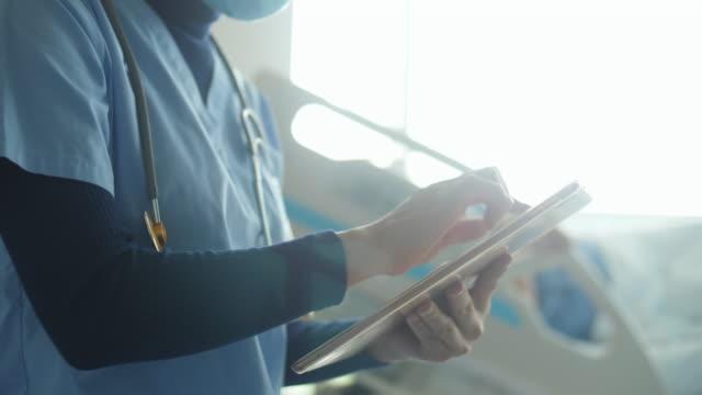arzt überprüft medizinische informationen und einsehen physikalischer bericht - portable information device stock-videos und b-roll-filmmaterial