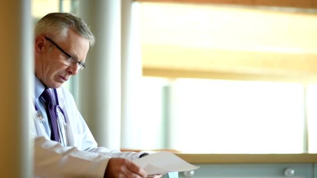 doctor checking notes in a hospital corridor